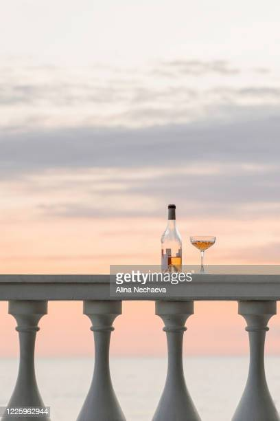 bottle of rose wine and beautiful wine glass on the white columns on sunset seascape view background - alina stock pictures, royalty-free photos & images