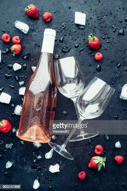 Bottle of rose wine, two empty wine glasses, icecubes, strawberries and raspberries on dark ground