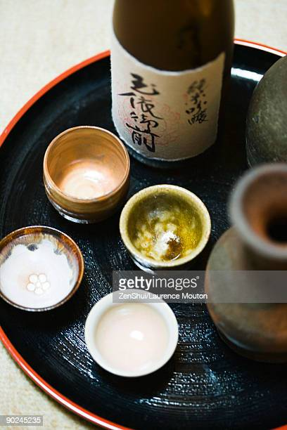 Bottle of sake and sake cups on tray, close-up