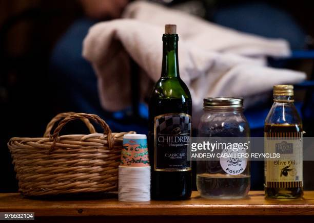 A bottle of strychnine red wine for communion and olive oil for blessings are seen before a Pentecostal serpent handlers service at the House of the...