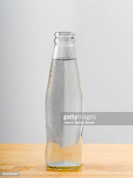 Bottle of water with the glass esmerilado with drops of water and a steam cloud frozen on a white bottom