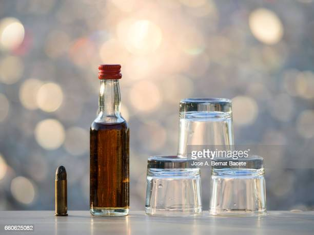 bottle of whiskey and  glasses of chupito close to a bullet , concept of which the alcoholism kills - alcoholics anonymous stock pictures, royalty-free photos & images