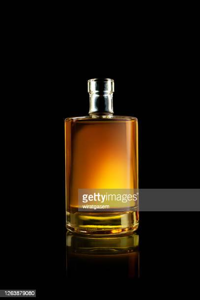 a bottle of whisky on reflective surface. - scotch whiskey stock pictures, royalty-free photos & images