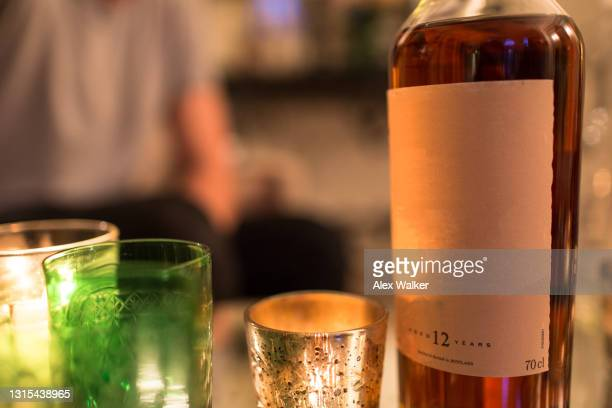 bottle of whisky with various ornate glasses and candles. - carving craft product stock pictures, royalty-free photos & images