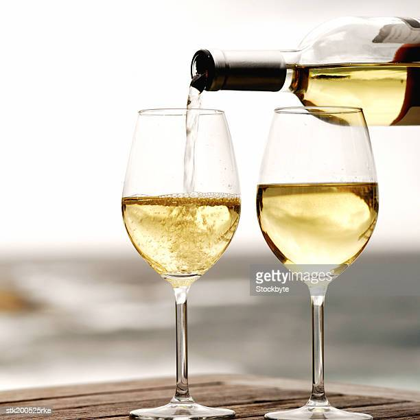 bottle of white wine being poured and two glasses