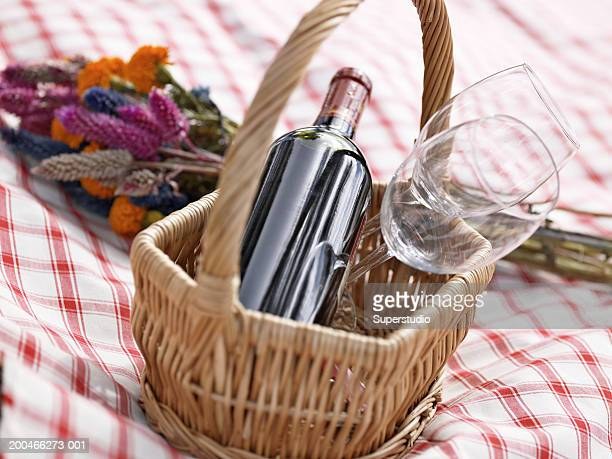 Bottle of wine and glasses in basket on checkered tablecloth