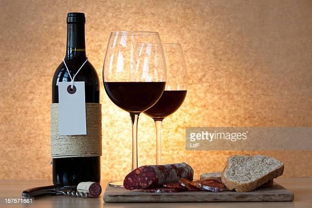 Flasche Wein und Gläser, salami und Brot.
