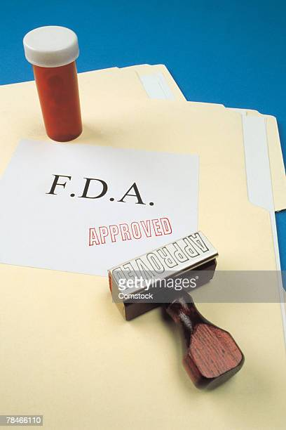 bottle on file folders with fda approved stamp - fda stock photos and pictures