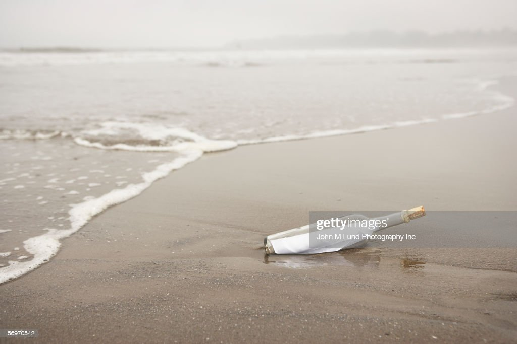 Bottle with message in sand at beach : Foto de stock