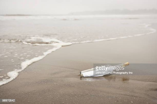 bottle with message in sand at beach - bericht stockfoto's en -beelden