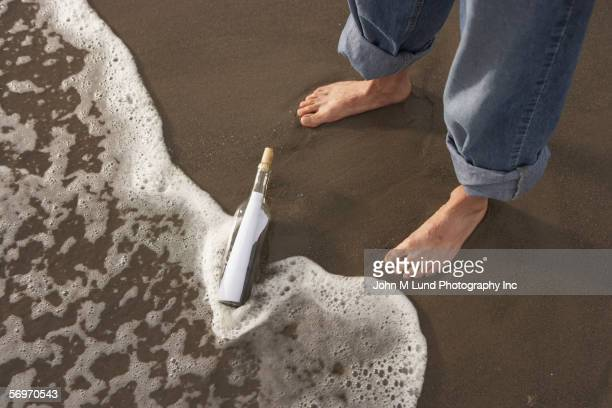 Bottle with message in sand at feet of man