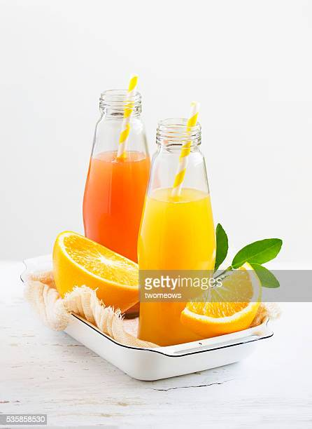 Bottled citrus fruit juice with drinking straw along side with cut citrus fruits family stacked on white background.