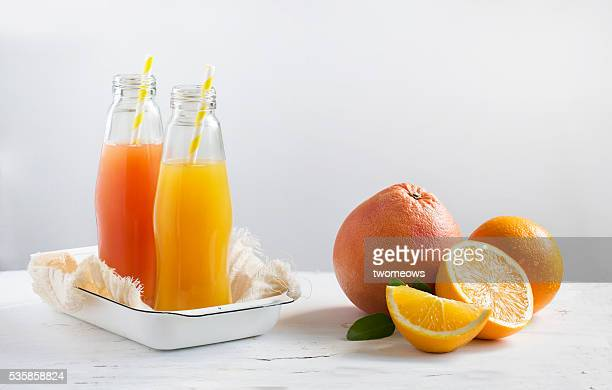 bottled citrus fruit juice with drinking straw along side with cut citrus fruits family stacked on white background. - naranja fotografías e imágenes de stock