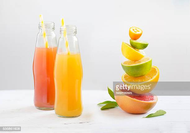 bottled citrus fruit juice with drinking straw along side with cut citrus fruits family stacked on white background. - ジュース ストックフォトと画像