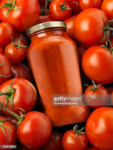 Bottled pasta sauce surrounded by tomatoes