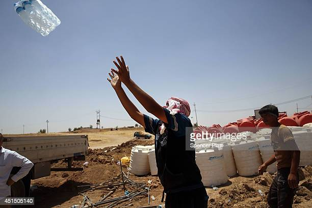 Bottled water is prepared for distribution at the Khazair displacement camp for those caughtup in the fighting in and around the city of Mosul on...