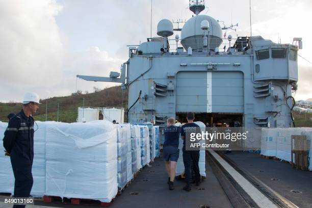 Bottled water is unloaded from the French marine frigate Germinal at the port of Galisbay on the French Caribbean island of Saint Martin on September...