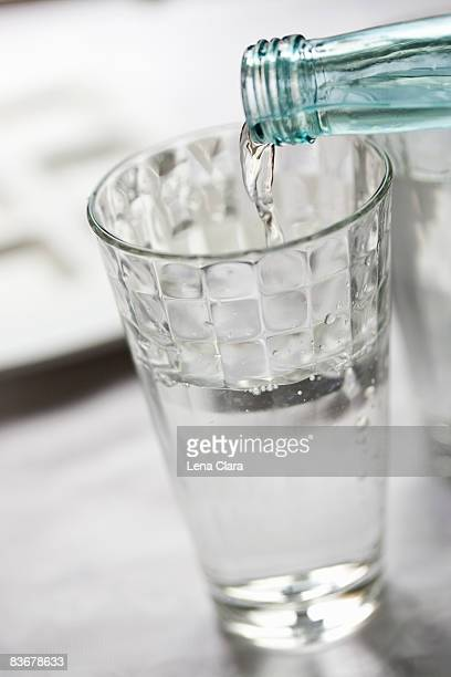 Bottled water pouring into a glass