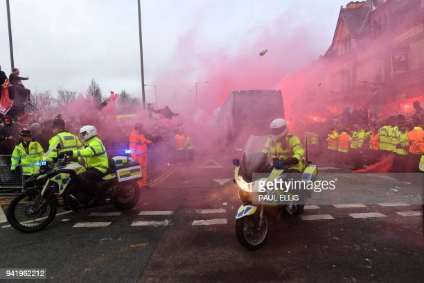 TOPSHOT Bottles and cans are thrown at the bus as Manchester City players arrive at the stadium before the UEFA Champions League first leg...