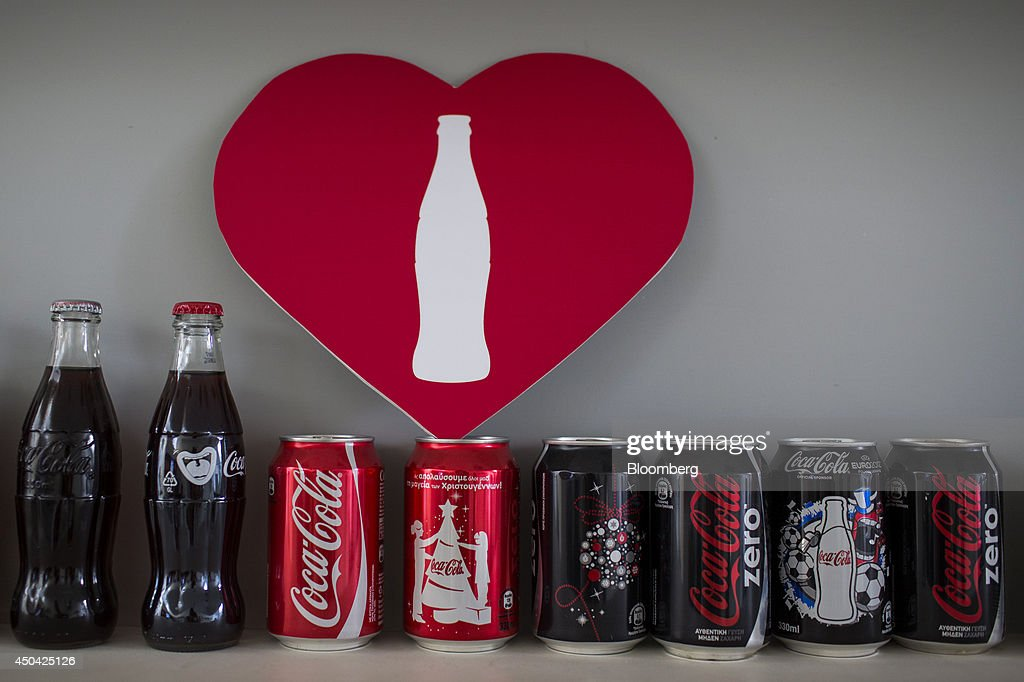 Bottles and cans of Coca-Cola beverages stand on display beneath a 'heart' sign in an office at the Lanitis Bros Ltd. bottling plant, part of the Coca-Cola Hellenic Group, in Nicosia, Cyprus, on Tuesday, June 10, 2014. Zug, Switzerland-based Coca-Cola Hellenic Bottling Co., which distributes Coca-Cola products in countries including Russia, wants to move away from using imported sugar for its Russian operations by 2015. Photographer: Andrew Caballero-Reynolds/Bloomberg via Getty Images
