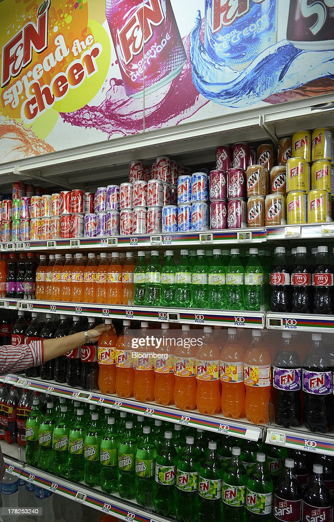 Bottles and cans of Fraser & Neave Ltd. (F&N) carbonated soft drinks are displayed for sale on a shelf in a supermarket in Singapore, on Wednesday, Aug. 28, 2013. Fraser & Neave, controlled by Thailands richest man Charoen Sirivadhanabhakdi, climbed the most in five weeks on plans to spin off its property business through a Singapore listing at the end of the year. Photographer: Munshi Ahmed/Bloomberg via Getty Images