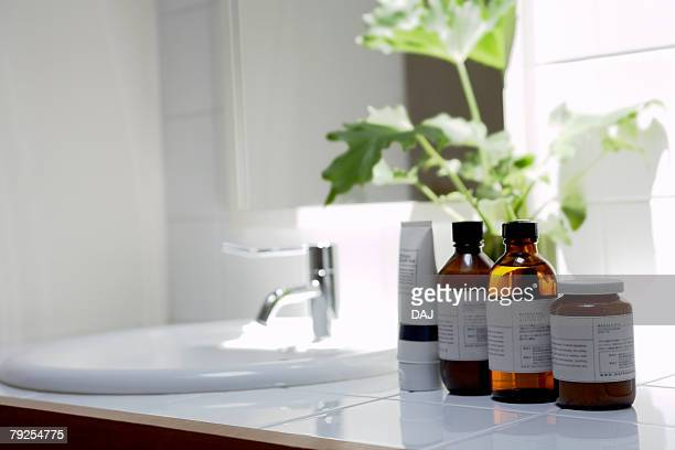 Bottles and mirror and sink in a white domestic bathroom