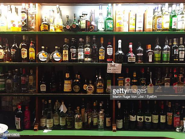 bottles arranged in liquor store - liquor store stock pictures, royalty-free photos & images
