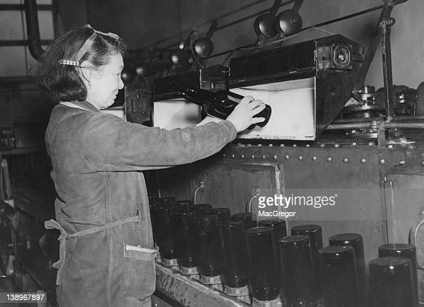 Bottles being examined for cleanliness under a strong light at the Whitbread brewery on Chiswell Street in the City of London 1947