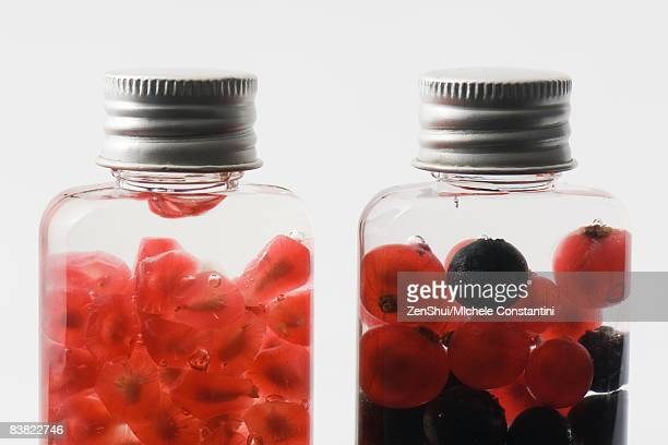 Bottles containing fresh berries and pomegranate seeds, close-up