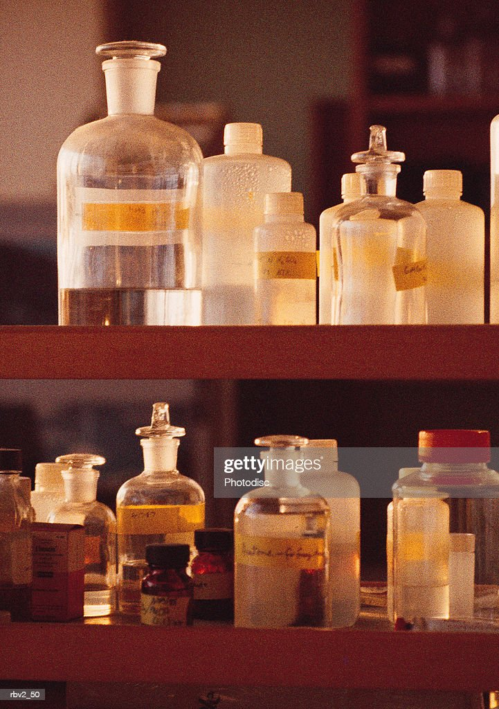 bottles filled with chemicals rest on laboratory shelves : Foto de stock