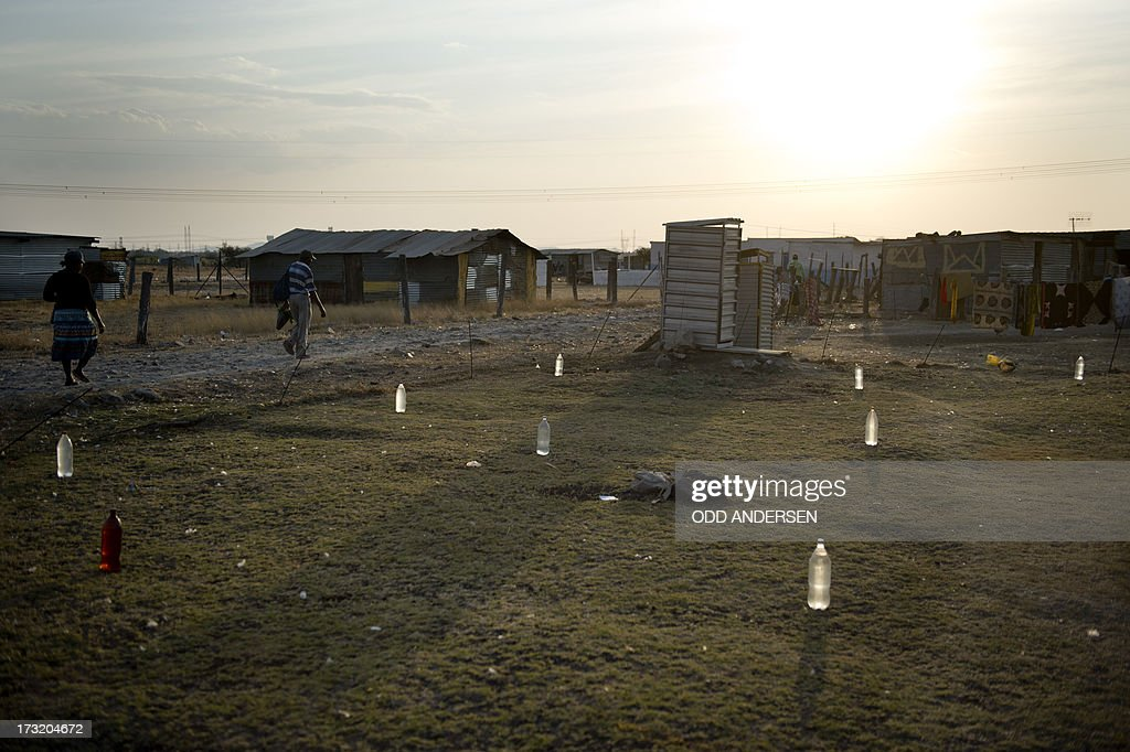 Bottles filled with water are laid out on a lawn to prevent stray dogs from fouling it on July 9, 2013 in the Nkaneng shantytown next to the platinum mine, run by British company Lonmin, in Marikana. On August 16, 2012, police at the Marikana mine open fire on striking workers, killing 34 and injuring 78, during a strike was for better wages and living conditions. Miners still live in dire conditions despite a small wage increase.
