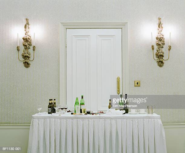 Bottles, half empty glasses and discarded food on buffet table