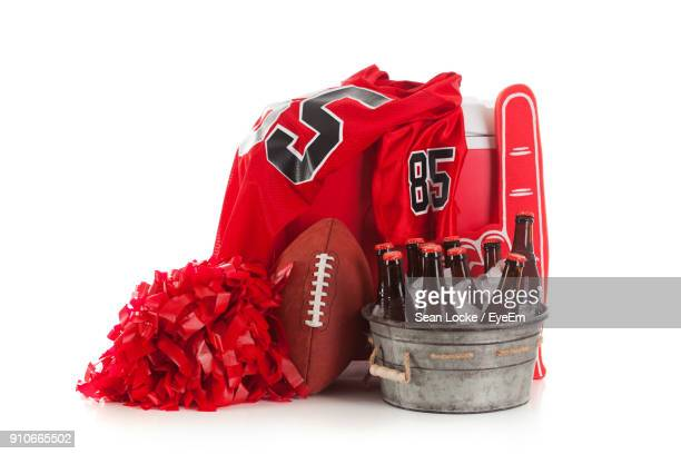 Bottles In Bucket By Rugby Ball With Red Pom-Pom Against White Background