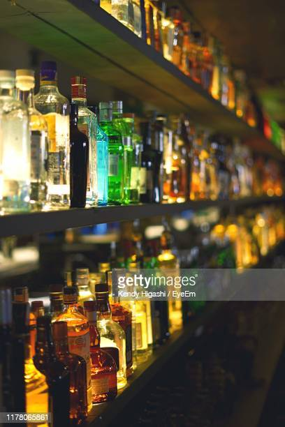 bottles in shelves - alcohol stock pictures, royalty-free photos & images