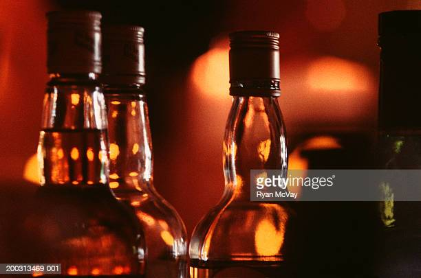Bottles of alcohol side by side on bar, close-up