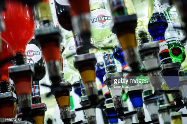 Bottles of alcoholic spirits such as Martini are seen mounted above Toni an automated cocktail maker made by Makr Shakr during a press event to...