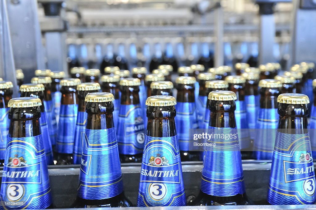Bottles of Baltika-branded lager move along a conveyor belt at the Carlsberg A/S production plant in Kiev, Ukraine, on Wednesday, March 14, 2012. Sales in the Ukraine were 'significantly higher,' helped by better economic conditions and the recent introduction of premium beers, while the U.K. saw 'continuing strong growth,' the brewer said. Photographer: Vincent Mundy/Bloomberg via Getty Images