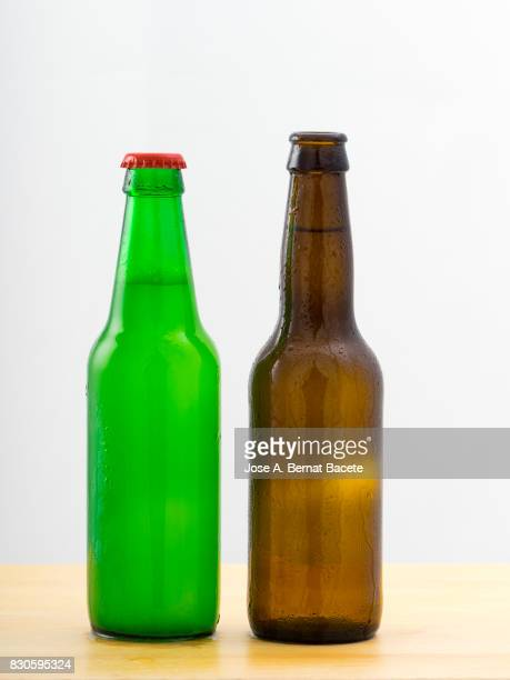 Bottles of  beer with the glass esmerilado with drops of water and a steam cloud frozen on a white bottom
