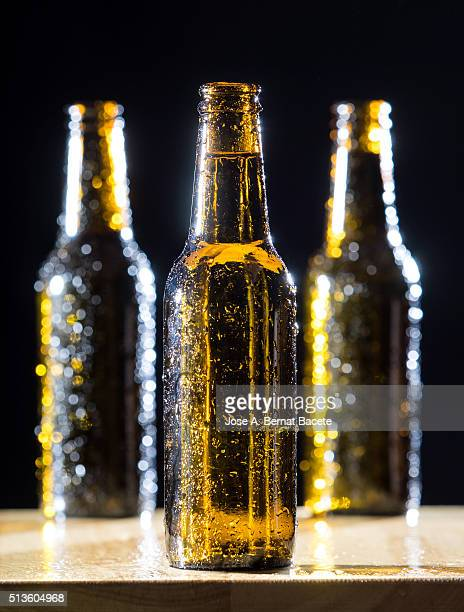 Bottles of beer with the glass misted on a table of wood