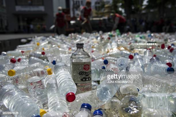Bottles of bootleg alcohol are ready to be destroyed after a recent raid in Surabaya on April 25, 2018. - In total around 100 Indonesians are...
