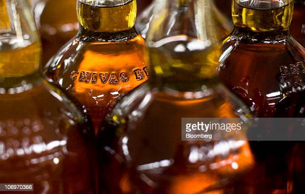 Bottles of Chivas Regal whisky travel along a conveyor belt at the Pernod Ricard SA bottling plant in Paisley UK on Thursday Nov 18 2010 Pernod...
