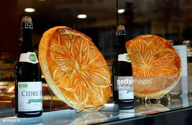 Bottles of cider and Epiphany cakes or Twelfth Night cakes are on display in the window of a pastry shop on January 06 2017 in Paris France The...