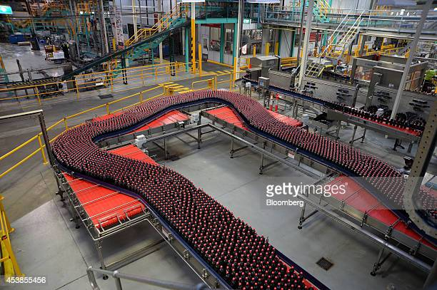 Bottles of CocaCola Classic move along a conveyor to the packaging area at a CocaCola Amatil Ltd production facility in Melbourne Australia on...
