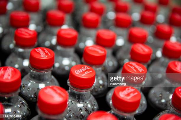 Bottles of CocaCola Co brand Coke carbonated soft drink sit inside the laboratory at the CocaCola Cambodia Bottling Plant operated by Cambodia...