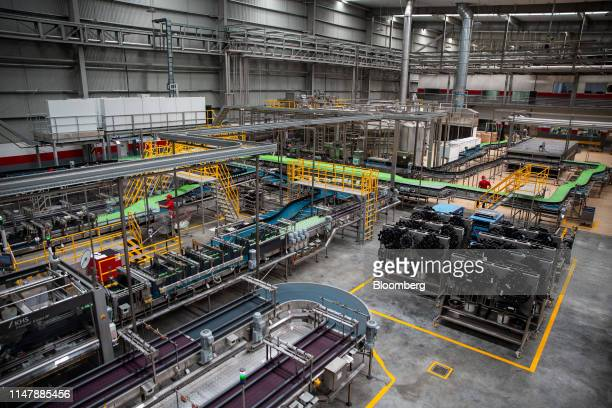 Bottles of CocaCola Co brand water move along a conveyor at the CocaCola Cambodia Bottling Plant operated by Cambodia Beverage Co which is a...