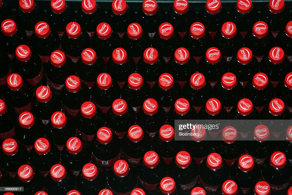 Bottles of Coca-Cola soda move along the production line at the Coca-Cola Co. bottling plant in Hmawbi, Myanmar, on Tuesday, June 4, 2013. Coca-Cola Co. Chief Executive Officer Muhtar Kent marked the return of the world's largest soda maker to Myanmar after 60 years by opening a bottling plant and pledging more investment in the newly opened economy. Photographer: Dario Pignatelli/Bloomberg via Getty Images