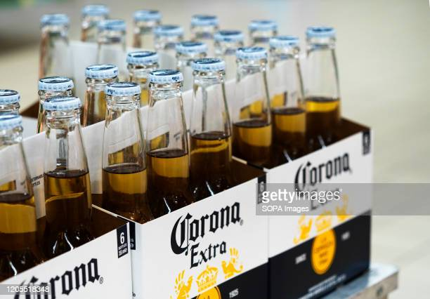 Bottles of Corona Extra beer are on a shelf in a store