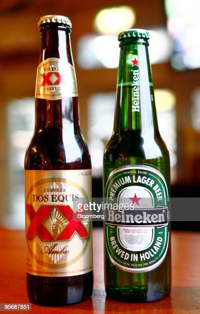 Bottles of Dos Equis left and Heineken beer sit arranged for a photograph in London UK on Monday Jan 11 2010 Heineken NV agreed to buy the beer...