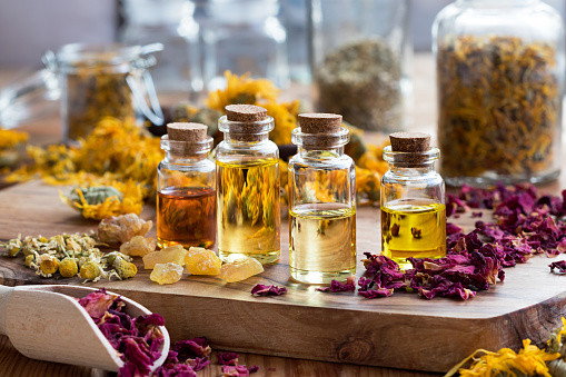 Bottles of essential oil with dried rose petals, chamomile, calendula and frankincense 899747886