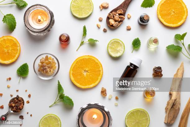 bottles of essential oil with fresh citrus fruit - sandalwood stock pictures, royalty-free photos & images